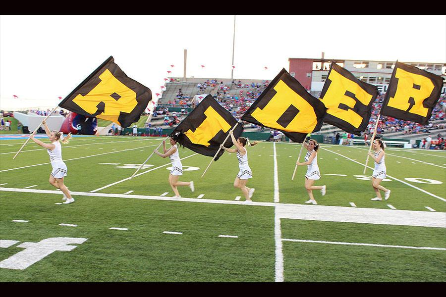 After a touchdown at the game against Abliene Cooper the cheerleaders take the flags that spell