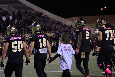 """Captains Hunter Kyle and TJ Vasher take Albin's hands, they walk together to meet the refs and begin the game with the coin toss. """"I had never been down on the field like that before,"""" Albin said. """"It takes a special heart to do something like what Coach Bindel did."""""""