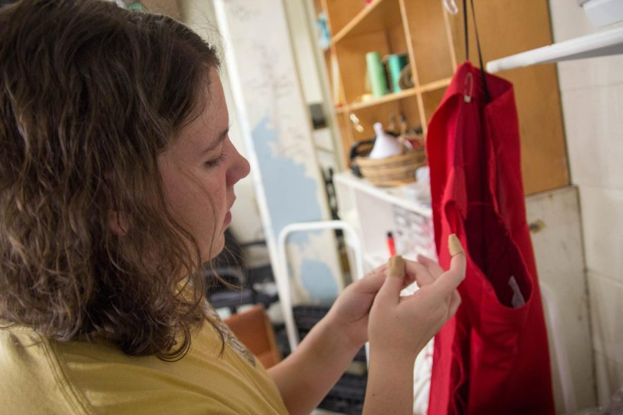 Erin Wisch works on a costume before the performance.