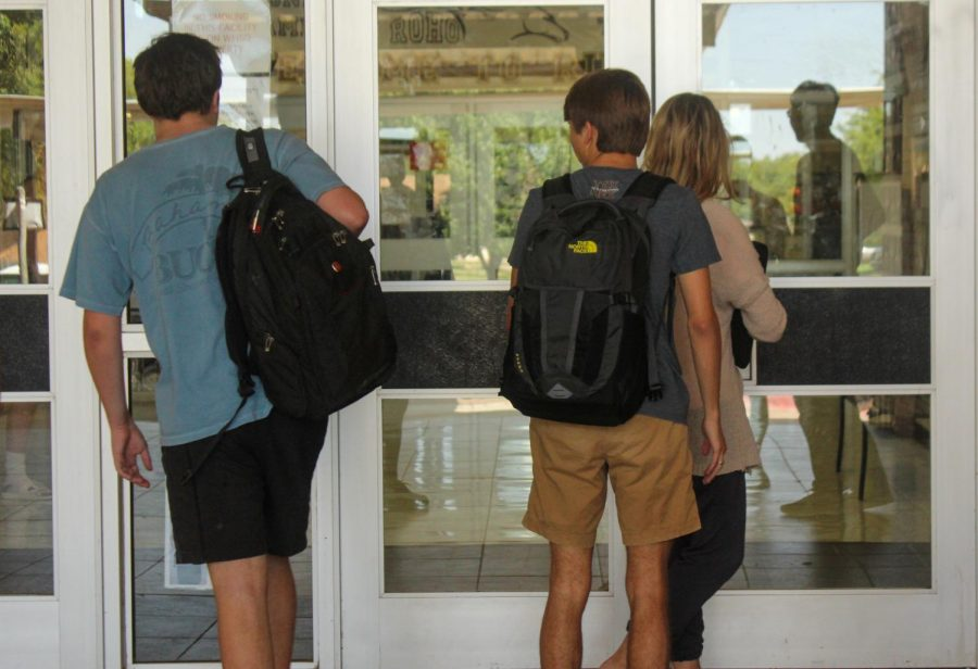 Students enter through the front doors after new policy change.