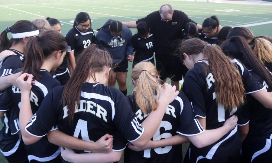 Before the game starts, the junior varsity B girls soccer team huddles together.
