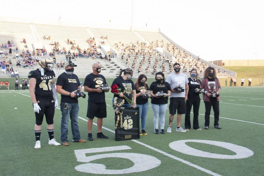 """Kaleb's family received a framed No. 42 jersey on Sept. 25, """"Kaleb Honea Night,"""" as the crowd honored his memory."""