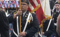 Elijah Aguon holds the American flag during a recent pep rally. Aguon is Riders highest-ranking JROTC officer.