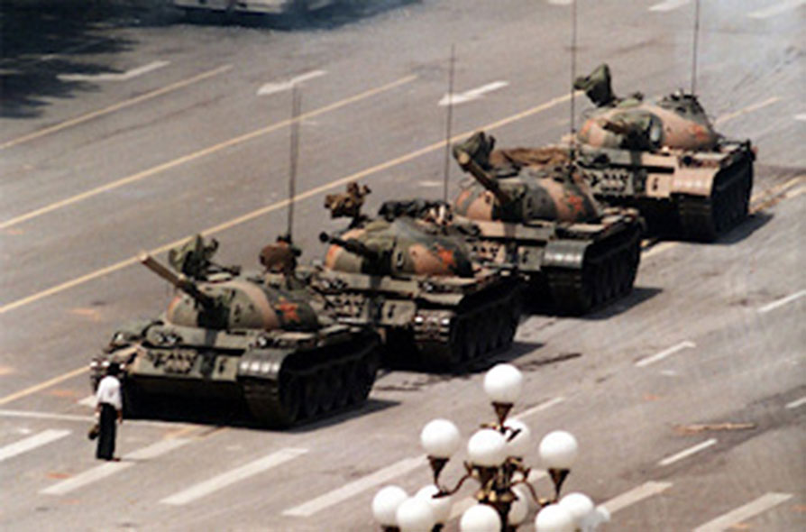 The most infamous photo of the Tiananmen Square massacre. Here a lone man stands in-front of a column of Chinese tanks. 4/15/1989