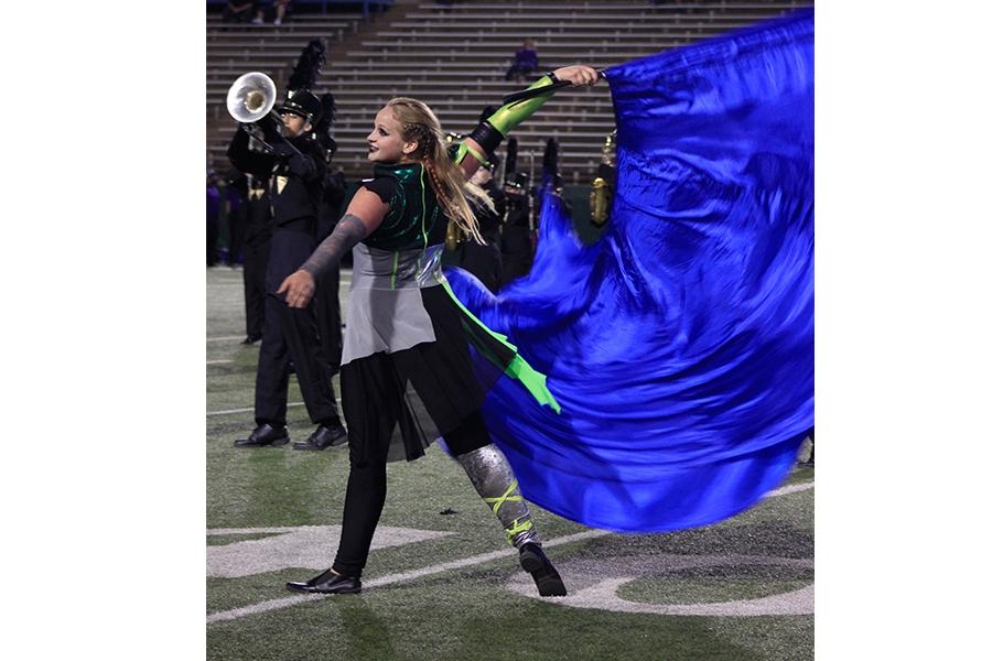 "Blue swing flags spin through the air during a halftime performance as senior Molly Whitaker performs. ""It's really fun performing with swing flags,"" she said. ""Except for the time I got the silk wrapped around my neck and almost choked to death during my solo."""