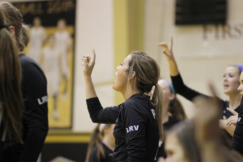 At the game against Old High, senior Libby Nelson holds a one in the air, cheering her team on as varsity only needs one point to win the match.