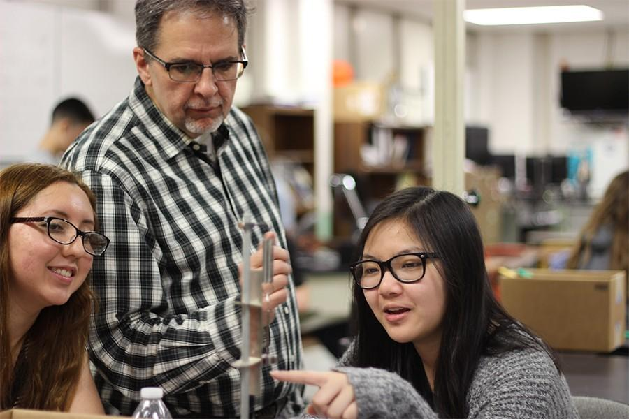 Mr. Baskin watches former students Ashley Flores and Lily Tran complete a lab in AP Physics 1.