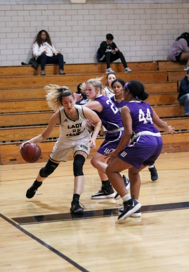 Senior Kaeli Donaldson tried to get away from three girls on the opposing team at a game during the 2019-2020 season.